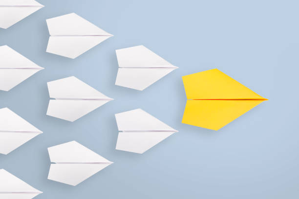 Leadership concepts with yellow paper plane leading among white stock photo