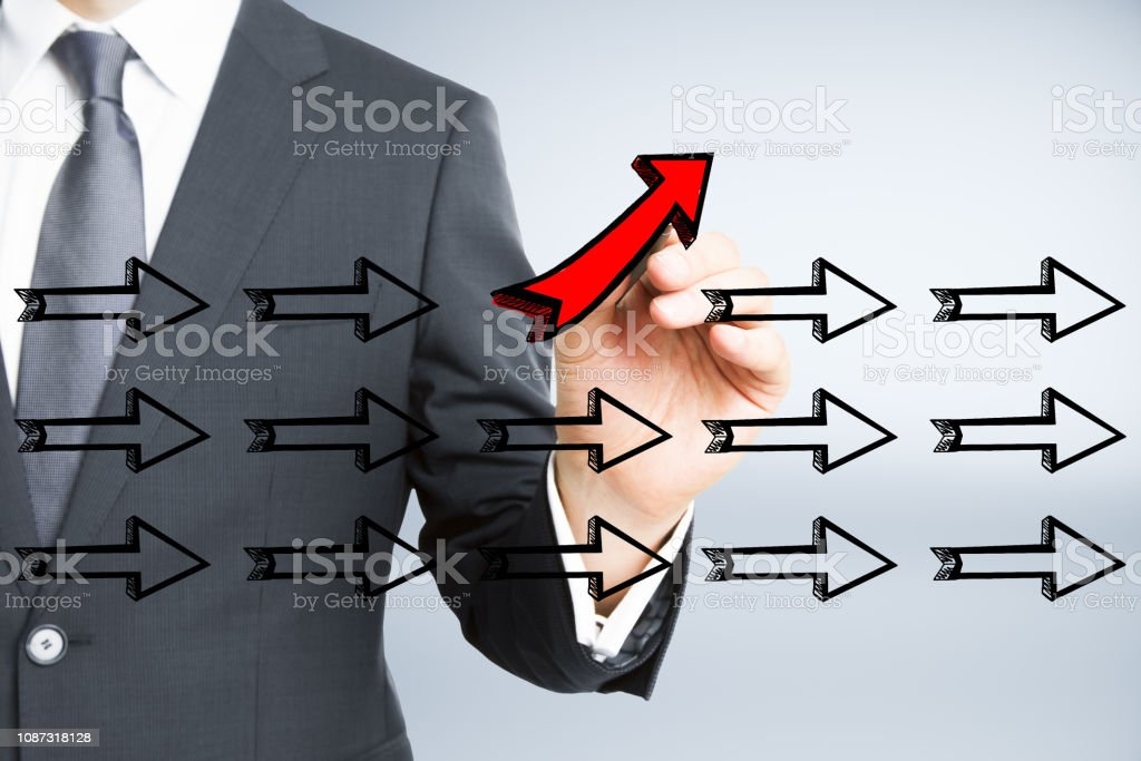 Businessman hand drawing different arrows on light background....