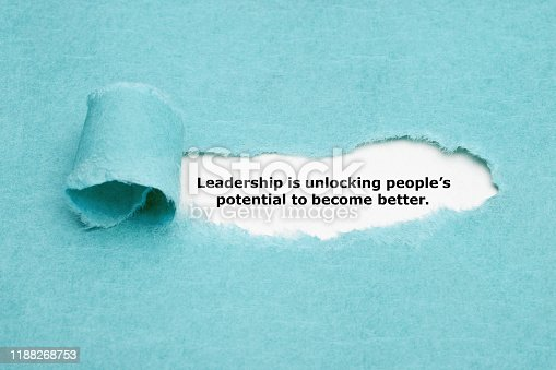 Motivational quote Leadership is unlocking peoples potential to become better appearing behind torn blue paper.