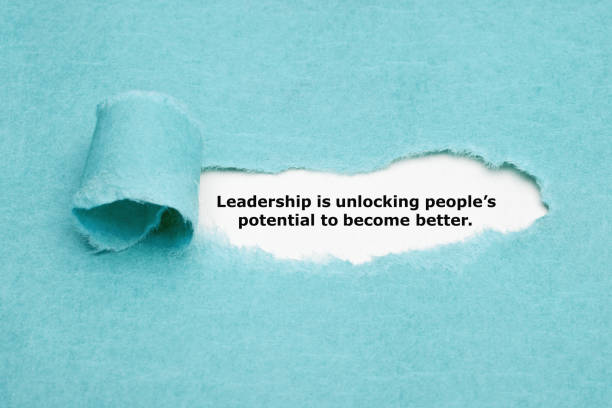 Leadership Is Unlocking Peoples Potential Motivational quote Leadership is unlocking peoples potential to become better appearing behind torn blue paper. anticipation stock pictures, royalty-free photos & images