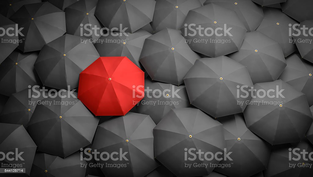 Leadership or distinction concept. Red umbrella and black umbrellas around. stock photo