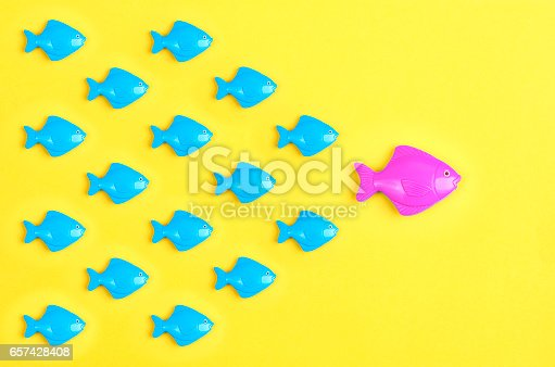 Concept of leadership demonstrated using toy fishes in yellow background
