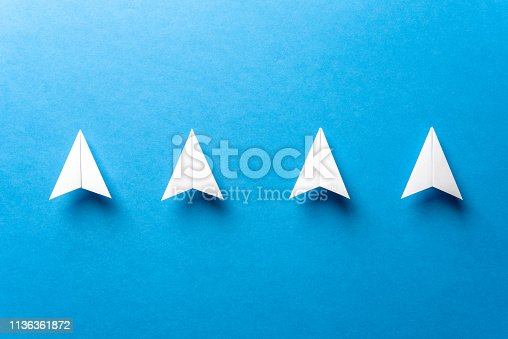istock Leadership, teamwork cooperation, motivation concept with a line of four white paper airplanes concept and negative space, on paper textured blue background. 1136361872