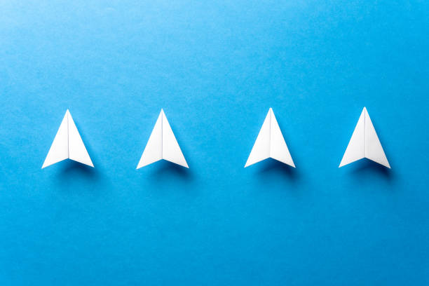 Leadership, teamwork cooperation, motivation concept with a line of four white paper airplanes concept and negative space, on paper textured blue background. stock photo