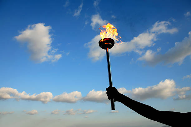 leadership torch silhouetted hand holding burning flaming torch over cloudy sky. flaming torch stock pictures, royalty-free photos & images