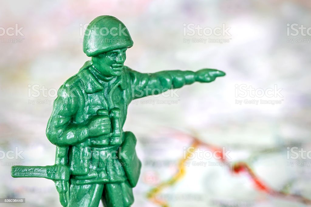 Leadership with little soldier toy on map aiming stock photo