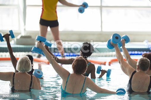 A multi-ethnic group of adults are in the public swimming pool and are taking a water aerobics class together. They have their arms raised in the air and they are holding floating dumbbells.