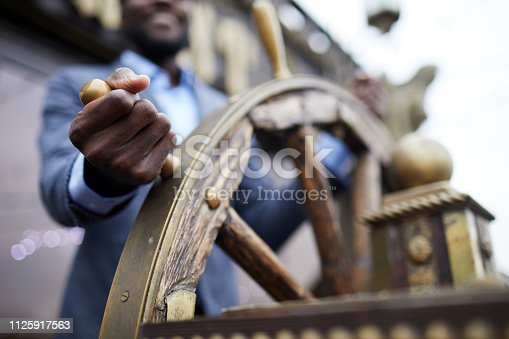 Hand of African-american business leader holding by large wooden sailing wheel while turning it