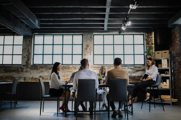 Leading team is inspiring and rewarding. Group of people having meeting at modern office market research stock pictures, royalty-free photos & images