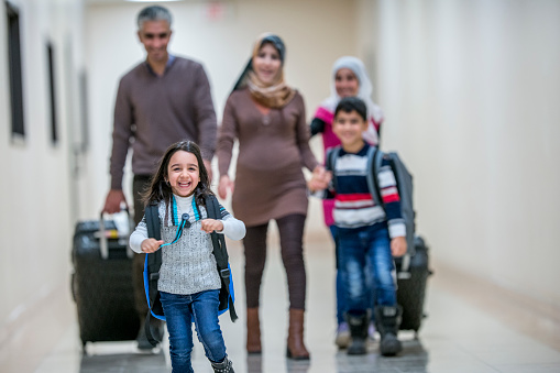 A Middle-eastern father, mother, brother and two sisters have just arrived to their new apartment building. They are carrying their luggage with them. They are walking down the hallway, being lead by the happy youngest daughter.