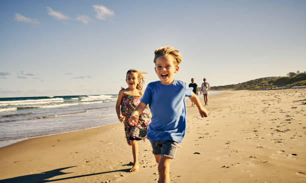 Leading the way to a day of fun Shot of two adorable little children running at the beach with their parents in the background sister stock pictures, royalty-free photos & images