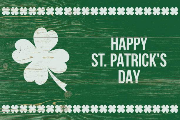 trébol de 4 hojas y texto blanco feliz día de san patricio sobre la pared de madera verde - día de san patricio fotografías e imágenes de stock