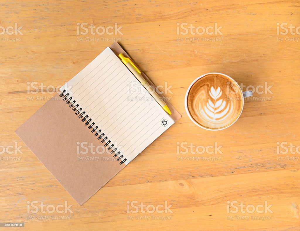 Leaf latte art coffee and notebook with pen stock photo