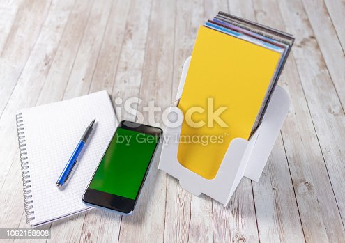 1062171194 istock photo Leaflet holder with a smartphone, notepad and pen 1062158808