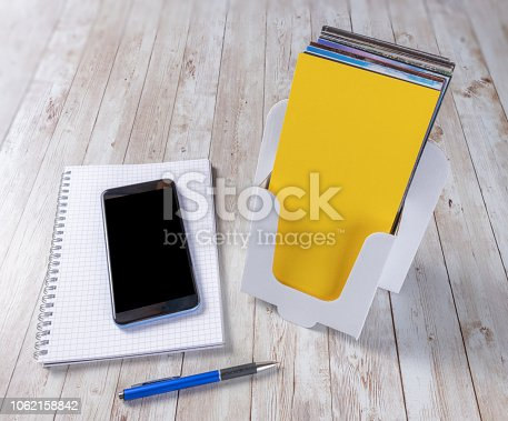 1062171194 istock photo Leaflet holder with a smartphone, notepad and pen 1062158842