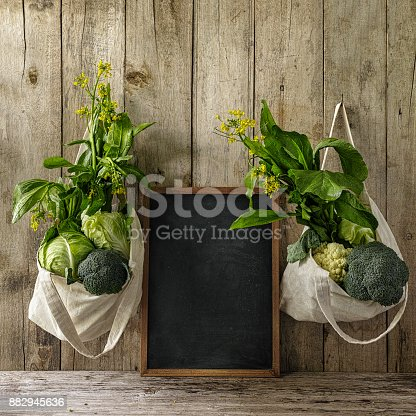 istock Leafy green vegetables hanging in reusable cotton bags, either side of a blackboard in the middle, on an old wood board wall background. 882945636
