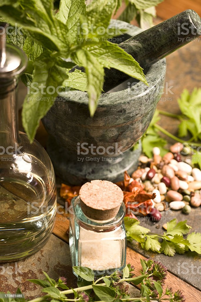 Leafy greens in stone mortar and pestle small jar in front royalty-free stock photo