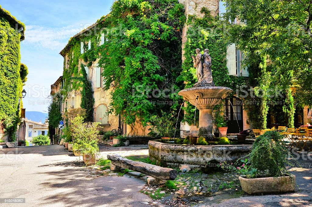 Leafy town square with fountain, Provence, France stock photo