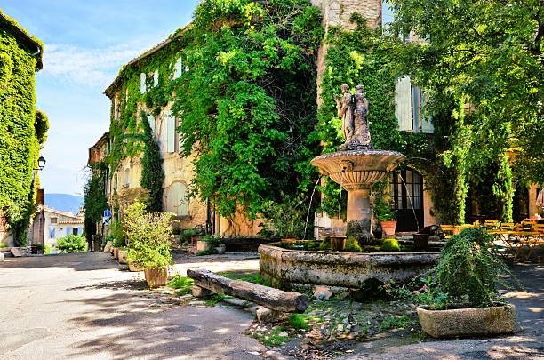 Leafy town square with fountain, Provence, France Leafy town square with fountain in a picturesque village in Provence, France provence alpes cote d'azur stock pictures, royalty-free photos & images