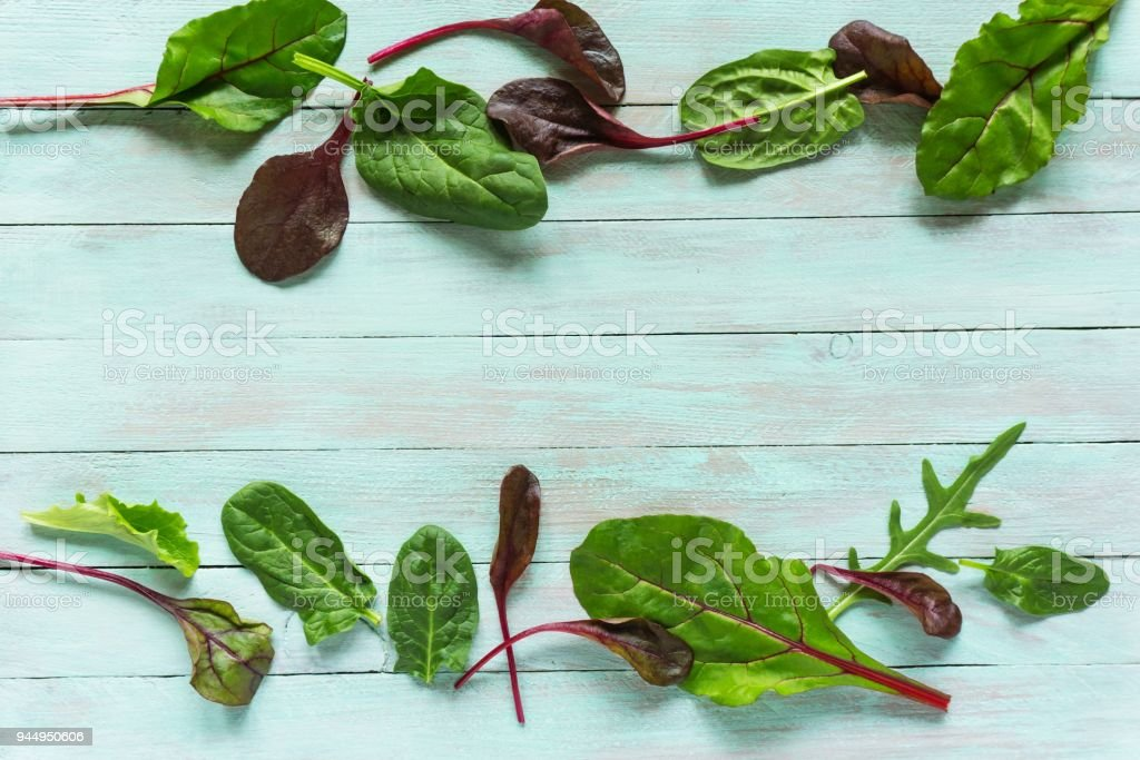 leafy vegetables, spinach and rukola on a wooden background stock photo