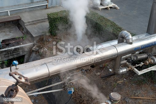 istock Leakage of steam in heat pipeline interior industrial gas with a lot of piping. Steam valve piping in factory 1023865432