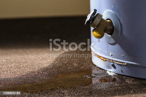 Water leaking from the plastic faucet on a residential electric water heater sitting on a concrete floor.
