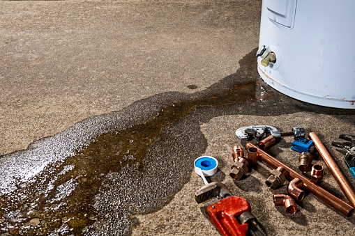 Water leaking from the plastic faucet on a residential electric water heater sitting on a concrete floor with a red pipe wrench, tubing cutters, teflon tape and copper fittings in the foreground to repair or place the appliance.