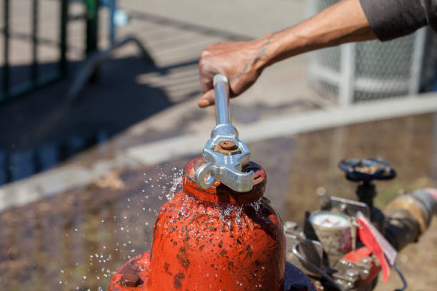 Leaking Fire Hydrant Spraying Water Being Closed with Wrench Leaking and Splashing Red Fire Hydrant Spraying Water Being Closed with Wrench fire hydrant stock pictures, royalty-free photos & images