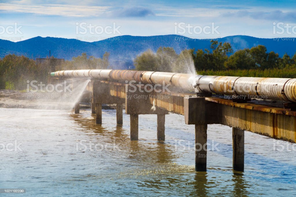 A leaking pipeline in the sun crossing a canal near the shoreline