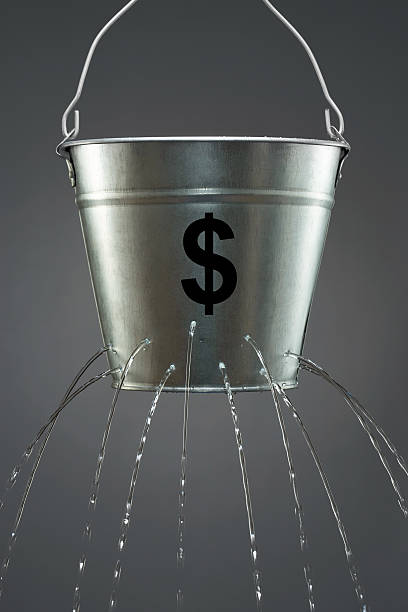 Leaky Dollar Bucket Leaky Dollar Bucket bucket stock pictures, royalty-free photos & images