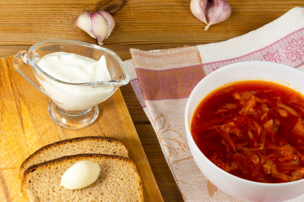 Lean borsch in a white bowl, sour cream, garlic and fresh rustic bread on a wooden table. Vegetarian food. Healthy lifestyle. stock photo