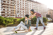Young woman pushing her friendon a longboard in urban city context - Concept of friendship and fun with new sport trends