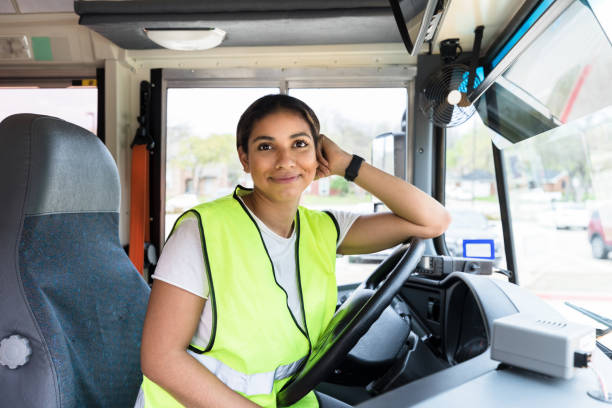 Leaning on steering wheel, cheerful bus driver smiles for camera stock photo