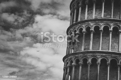 Close-up image of the leaning tower of Pisa, and in the far background a Plane taking off from the airport.