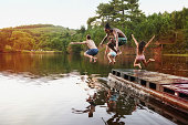 Shot of a group of teenage friends jumping off a pier into a lake
