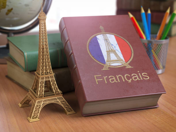 Learn and studiyng French concept. Book with  French flag and Eiffel tower on the table. Learn and studiyng French concept. Book with  French flag and Eiffel tower on the table. 3d Iluustration french culture stock pictures, royalty-free photos & images