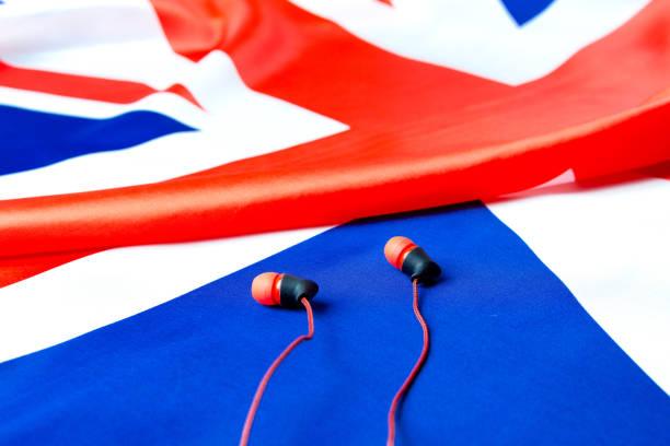lernen sie englisch. britische flagge und kopfhörer nahaufnahme. das konzept der e-learning englisch. - lautsprecher test stock-fotos und bilder