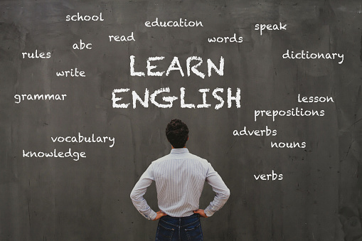 learn english concept, business man looking at word cloud on chalk board