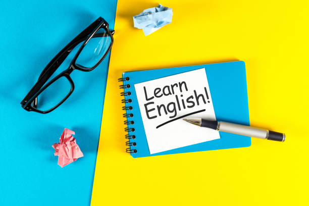 Learn english - note at blue and yellow background with teachers glasses Learn english - note at blue and yellow background with teachers glasses. reference book stock pictures, royalty-free photos & images
