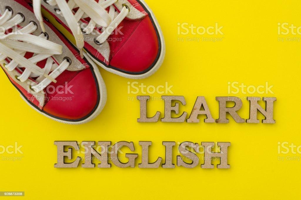 Apprendre l'anglais, les mots en lettres en bois avec fond jaune en face de baskets rouge jeunesse - Photo
