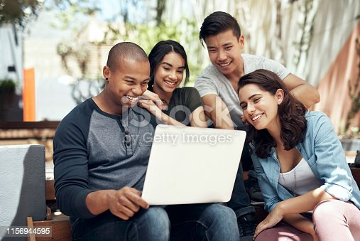 Shot of a group of young men and women using a laptop together on campus