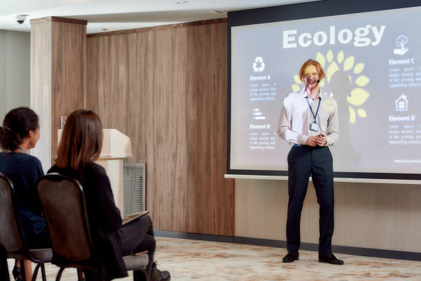 learn here. full-length shot of young male speaker in suit with headset and laser pointer showing the presentation on a screen while giving a talk at business meeting, ecological forum - theatre full of people stage foto e immagini stock