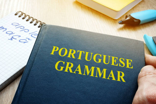 Learn portuguese grammar. Hand is holding book. stock photo