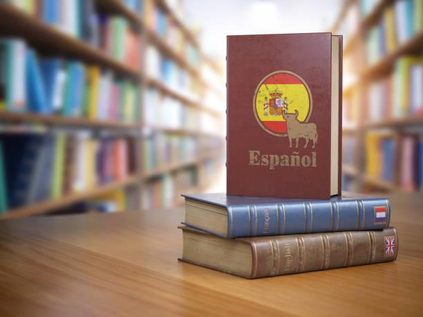 lernen sie spanisch konzept. spanisches wörterbuch buch oder textbok mit flagge von spanien und kuh auf dem cover in der bibliothek. - spanisch translator stock-fotos und bilder
