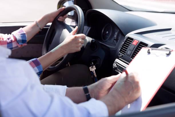 Lernende Fahrerschülerin fährt Auto mit Fahrlehrer – Foto