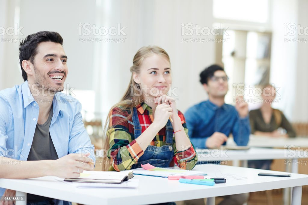 Learners by desk stock photo