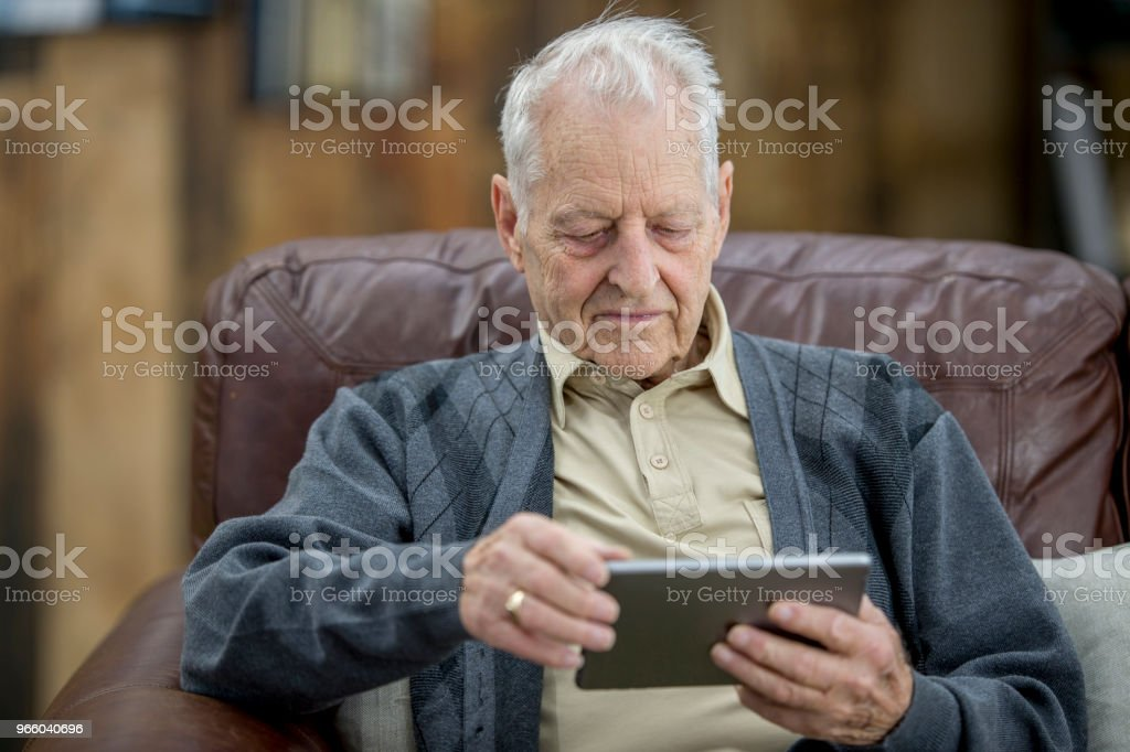 Learning About Technology An elderly Caucasian man is indoors in his house. He is sitting on the couch and learning to use a tablet computer by himself. 80-89 Years Stock Photo