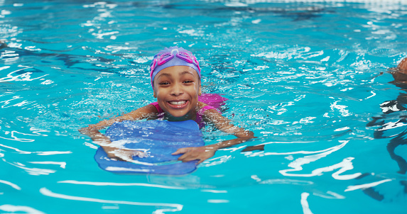 Portrait of an adorable young girl using a board during a swimming lesson