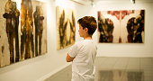 9 years old boy visiting an art gallery and looking to the paintings…