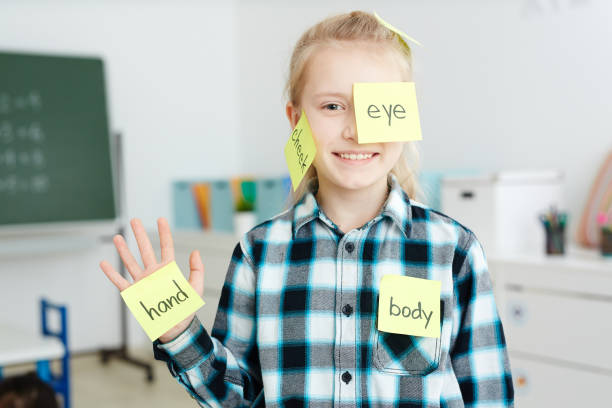Learning body parts Happy schoolgirl having sticky notepapers with English names of body parts on her hand, cheek and eye english language stock pictures, royalty-free photos & images